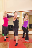 Unga kvinnor som utför sträcka övningar i idrottshall Royaltyfri Fotografi