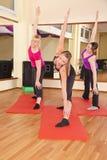 Unga kvinnor som utför sträcka övningar i idrottshall Royaltyfria Bilder