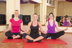 Unga kvinnor som utför yogaövningar i idrottshall Royaltyfri Foto