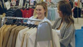 Unga kvinnor som väljer kläder som hänger på kuggarna Royaltyfri Fotografi
