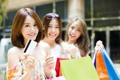 unga kvinnor som visar den shoppingpåsar och kreditkorten arkivfoto