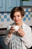 Unga kvinnor står i köket med kaffe Royaltyfri Foto