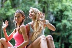 Unga kvinnor vilar på vaggar i djungelvattenfallet i bakgrunden Royaltyfri Bild