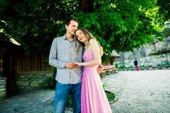 Unga kyssande par under stort träd med gunga Royaltyfria Bilder