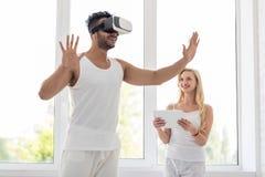 Unga latinamerikanska Digital för virtuell verklighet för mankläder exponeringsglas, lycklig le flicka som använder minnestavlan royaltyfri foto