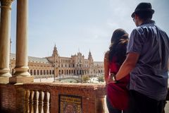 Unga latinska par som ser Plaza de España Sevilla i Spanien fotografering för bildbyråer
