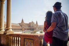 Unga latinska par som ser Plaza de España Sevilla i Spanien royaltyfri foto