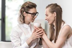 Unga le kvinnor som tillsammans rymmer kaffekoppen Royaltyfria Bilder