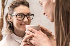 Unga le kvinnor som tillsammans rymmer kaffekoppen Royaltyfri Fotografi