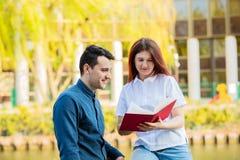 Unga le studenter som rymmer utomhus böcker arkivfoton