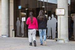 Unga lesbiska par som tillsammans går in mot den val- högskolan på den spanska riksdagsvaldagen i Madrid, Spanien Arkivfoto