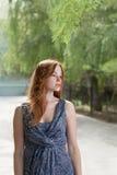 Unga ljust rödbrun haired kvinnor som poserar yttersidan i stad, parkerar Royaltyfria Bilder
