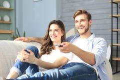 Unga ?lska par p? tv och att skratta f?r soffa hemmastadd h?llande ?gonen p? arkivfoton