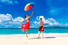 Unga lyckliga älska par som har gyckel i den tropiska stranden med Royaltyfria Bilder