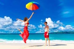 Unga lyckliga älska par som har gyckel i den tropiska stranden med Royaltyfria Foton