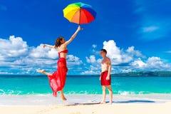 Unga lyckliga älska par som har gyckel i den tropiska stranden med Royaltyfri Bild