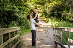 Unga lyckliga älska par tycker om ett ögonblick av lycka i skog arkivbilder