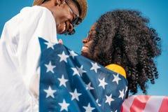 unga lyckliga afrikansk amerikanpar med Amerika sjunker att krama Royaltyfria Foton