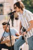 Unga lyckliga buskers handelsresande och gitarrist som spelar musik arkivfoto