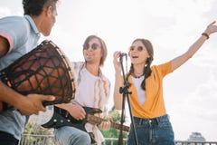 Unga lyckliga buskers som har gyckel som spelar musik och att sjunga arkivbilder