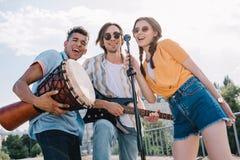Unga lyckliga buskers som sjunger vid mikrofonen arkivbilder