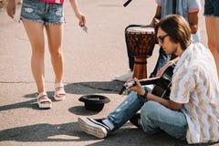 Unga lyckliga buskers som spelar en improviserad konsert på gatan och att motta för stad arkivbilder