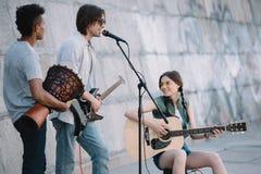 Unga lyckliga buskers som spelar musik och att sjunga royaltyfri fotografi