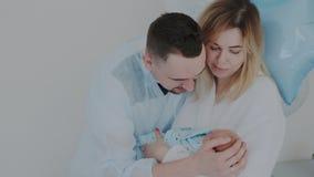 Unga lyckliga föräldrar ger en nyfödd affektion och omsorg Lycklig familj i sjukhus efter barnsbörd arkivfilmer