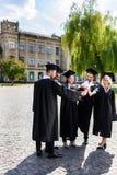 unga lyckliga graderade studenter som gör laggest royaltyfria bilder