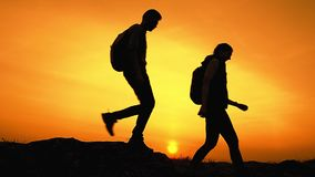 Unga lyckliga handelsresande som fotvandrar med ryggs?ckar p? Rocky Trail p? sommarsolnedg?ngen Familjlopp- och aff?rsf?retagbegr arkivfilmer