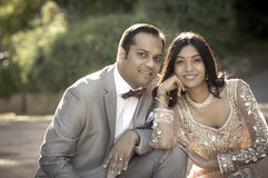 Unga lyckliga indiska par som tillsammans utomhus sitter Royaltyfri Foto