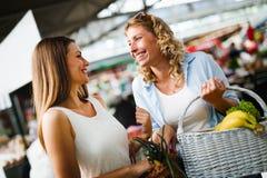 Unga lyckliga kvinnashoppinggrönsaker och frukter på marknaden royaltyfri fotografi