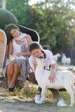 Unga lyckliga kvinnor med katten och geten på lantgård Arkivfoton