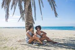 Unga lyckliga kvinnor som kopplar av på stranden under gömma i handflatan Royaltyfri Bild