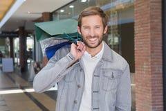 Unga lyckliga le hållande shoppingpåsar för man Royaltyfria Foton
