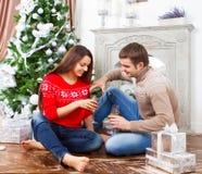 Unga lyckliga le par vid det Cristmas trädet Royaltyfri Foto