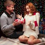 Unga lyckliga le tillfälliga par som gör en present Royaltyfri Foto