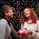 Unga lyckliga le tillfälliga par som gör en present Royaltyfri Fotografi