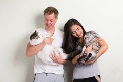 Unga lyckliga mång--person som tillhör en etnisk minoritet par som tillsammans rymmer två katter mot vit bakgrund arkivbilder