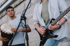 Unga lyckliga manliga buskers som spelar gitarren och djembe arkivfoto