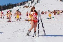 Unga lyckliga nätta kvinnor på ett berg skidar i färgrik bikini Arkivfoto