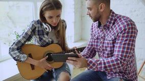 Unga lyckliga och älska par studerar för att spela den akustiska gitarren genom att använda minnestavladatoren och ha gyckel, med royaltyfri bild