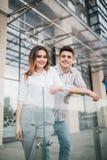 Unga lyckliga par att koppla av och ha gyckel på balkongen i deras nya hem- lägenhet arkivfoton