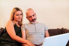 Unga lyckliga par genom att använda bärbara datorn i soffa och tycker om hemma arkivbilder