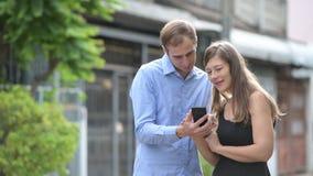 Unga lyckliga par genom att använda telefonen tillsammans utomhus arkivfilmer