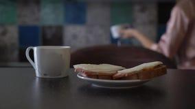Unga lyckliga par i den moderna lägenheten som har frukosten tillsammans arkivfilmer