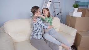 Unga lyckliga par i en ny lägenhet Begreppet av köpande eller hyr en ny egenskap lager videofilmer
