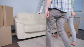 Unga lyckliga par i en ny lägenhet Begreppet av köpande eller hyr en ny egenskap stock video