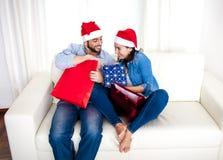 Unga lyckliga par i jultomtenhatt på jul som rymmer shoppingpåsar med gåvor Royaltyfri Foto