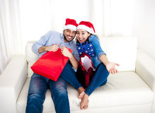 Unga lyckliga par i jultomtenhatt på jul som rymmer shoppingpåsar med gåvor Arkivfoton